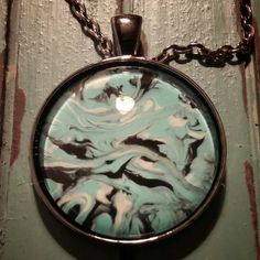 New item on Prettysmelly.com. this is a glass pendant with a light blue, black and white design