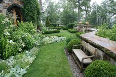 white, silver & green plantings with stone walls and garden seats upon pebbled sitting areas