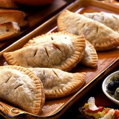 Empanadas: The perfect finger food for your tapas tasting, these warm, crisp turnovers are filled with a spicy mixture of turkey, almonds, olives, and raisins. #gogourmet