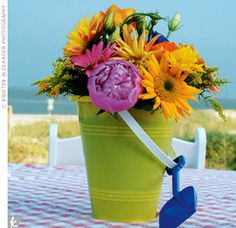 Sand bucket flower centerpiece. Could be cute for kids table.