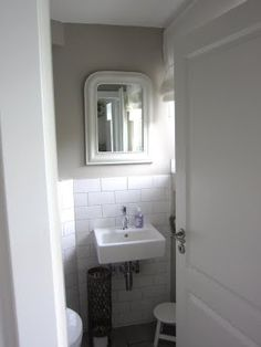 Cloakroom. White tiles with white grouting and grey walls