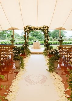 This tent wedding ceremony has a gorgeous landscape for background view. Lovely Chuppah and decorated aisle