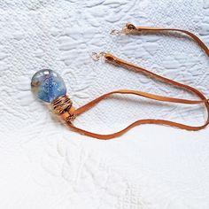 Talismã: é um colar longo de design contemporâneo e esportivo. Um cordão de couro natural em cor caqui, termina em um pingente artesanal de vidro tipo murano.