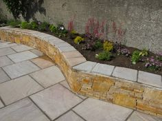 Raised planting bed with quartz stone and sandstone wall capping.