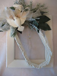 Shabby chic wreath made from vintage frames, has glass prism hanging in center,.