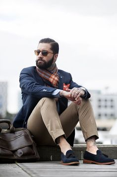 Shop this look on Lookastic: https://lookastic.com/men/looks/blazer-chinos-tassel-loafers-messenger-bag-pocket-square-scarf-sunglasses/6753   — Brown Sunglasses  — Orange Plaid Scarf  — Orange Print Pocket Square  — Navy Blazer  — Khaki Chinos  — Dark Brown Leather Messenger Bag  — Navy Suede Tassel Loafers
