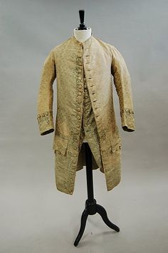 A gentleman's frock coat and waistcoat, woven to shape, 1760s, of ivory silk woven with blue foliate lattice and blooms, the coat buttoning from neck to hem