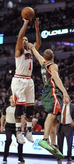 Chicago Bulls' Derrick Rose (1), goes up for a shot against Milwaukee Bucks' Luke Ridnour (13), during the second half of an NBA preseason basketball game in Chicago, Monday, Oct. 21, 2013. Chicago won 105-84. (AP Photo/Paul Beaty)