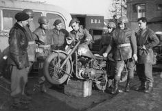 THE POLISH ARMY IN THE NORTH-WEST EUROPE CAMPAIGN, 1944-1945 - Staff Sergeant of the Royal Army Service Corps inspecting a Matchless motorcycle in use by despatch riders of the 1st Polish Armoured Division. Standing by are some of the riders and the Polish Workshop Officer. North Brabant, Holland, 11 January 1945.