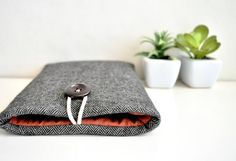 Classic herringbone custom size Phone Pouch. Classic herringbone covers the body of the sleeve. This phone pouch is padded and custom fit for your phone. Lining is spice red cotton fabric. String and wooden button closure on top. Soft foam padding keeps your android or iPhone comfy and