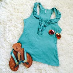 Teal razorback tank with ruffle/button detail! Teal razorback tank with ruffle/button detail! Bought at a boutique and was a little overpriced, but good quality.  Has one small stain on the back left side (see last picture). No other tears or stains!  Tresics Tops Tank Tops