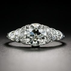 A classic Art Deco step motif is artfully softened with sensuous curves in this strikingly stunning engagement ring beautifully hand fabricated in platinum, circa 1920s-30s. The shining star, however, is a bright and brilliant European-cut diamond, imbued with just a touch of warmth, weighing 1.54 carats (accompanied by a GIA Diamond Grading Report stating: N color - VS1 clarity). A delightfully distinctive original Art Deco dazzler. Currently ring size 7 1/4.
