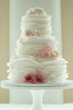 Wedding cake. 3 tier white ruffled icing with oink flowers