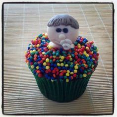Cupcake Bebê na Piscina de Bolinhas | Cupcake bebê na piscina de bolinhas, cobertura de chocolate, confeitos coloridos e pasta americana. Sabor do recheio e da massa do bolo de sua preferência.
