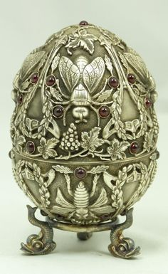 Russian silver egg adorned with cabochon garnets and raised design depicting bees, leaves and grape clusters with vines. Gold wash to interior. Makers marks [Pavel Ovchinnikov] to both pieces of the egg. Late 19th century.