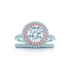 This ring is classically elegant with a round brilliant white diamond encircled by a row of pink and white bead-set diamonds. A diamond band enhances the striking magnificence of this piece.
