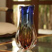 Shaped like a blossoming bud, this vase is alive with the colors of dusk. Bright red and orange converge into the last sunray under a sapphire blue sky. Captured within a glass frame, the illusion is sublime. Murano artisans craft this vase with ancestral blown glass techniques, enabling them to recreate the beauty of a sunset.