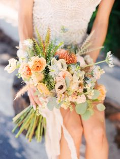 loose and unstructured bridal bouquet is wrapped in cream muslin and is made of orange protea, light blue nigella, blue thistle, white anemone, peach stock, white scabiosa, Juliet garden rose, silver dollar eucalyptus, and peach ranunculus and