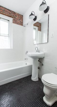 Modern Midtown white and black bath features leveled hexagonal tiled floors, glossy white subway wall tiles, exposed brick wall, and pedestal sink.