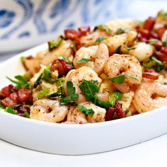 Shrimp & Grits - 1 C. stone-ground grits; 3 T. butter; 2 C. shredded fontina cheese; Cayenne pepper; 1 lb. shrimp, peeled and deveined; 1/2 lb. bacon, chopped; 1/2 lemon, juiced; 2-3 T. chopped parsley; 3/4 C. chopped green onions; 1 large garlic clove, minced; Salt and Pepper
