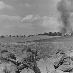 3 Waffen-SS soldiers with their MG-34 as they look towards a burning building somewhere in Russia. Summer of 1941.