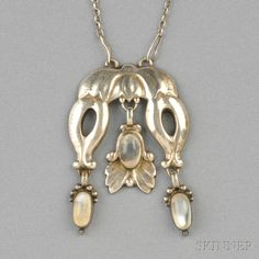 .830 Silver and Moonstone Pendant, Georg Jensen, the bud motifs set with moonstone cabochons, suspended from paperclip chain, no. 17, lg. 2 in., signed GI/830/S impressed in a circle of dots, and Georg Jensen in impressed circle of dots.
