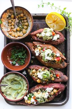 mediterranean stuffed sweet potatoes with marinated chickpeas and topped with an avocado tahini sauce, (grain-free & vegan).