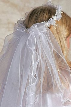Ariana Lily & Bead First Communion Veil (22402) - Here is a halo of sheer ribbon wisps and floral springs for your angel to wear on her Holy Communion day. This Communion veil is beautiful from any view, front or back. A sheer double bow back adorned by a single white beaded flower has a multitude of ribbons cascading below it, while drops of pearls scatter across the double layered veil. Absolutely gorgeous!