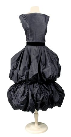 Gres Two-Tiered Bubble Dress   French, mid 1950s   Of black silk tissue taffeta, sleeveless bodice with original decollete neckline inset with faux bib and bateau neckline at a later date, bib yoke, black velvet ribbon waistband to tie at back, double bubble skirt