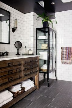 We love this black and white industrial bathroom. The white subway tile looks amazing paired with the wooden vanity.