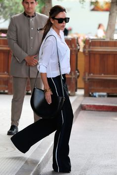 12 May Victoria Beckham was seen leaving her hotel wearing a classic white shirt with wide-leg tailored trousers. - HarpersBAZAAR.co.uk