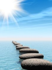 row of stones in water with sun beam stock photo