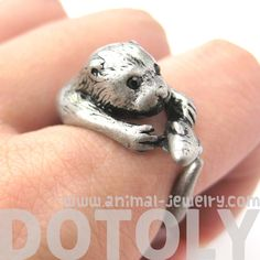 otter outdoor art | Otter-holding-a-fish-shaped-animal-wrap-around-ring-in-silver-us-sizes ...