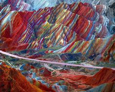 """The jaw-dropping rocky landscape is naturally red from a build-up of sandstone over many millions of years, while the rainbow effect comes from colourful mineral deposits. Sandstone and red mineral deposits were compressed into multi-coloured layers of rock. Movement of the giant plates that form Earth's crust pushed, cut, and folded the layers. The name Danxia means """"rosy clouds"""" in Chinese."""