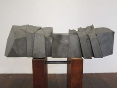 10 pieces of grey stone ganged together sit in an unstable manner on top of two dark cherry pieces of wood