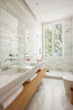 In this modern bathroom theres a wooden bathroom vanity with open shelving, that has double sinks with tall rectangular mirrors above each one. A glass shower surround allows the light from the vertical windows to pass through and fill the room, while stone tile adds a soft natural touch to the space. #doublebathroomsink