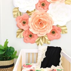 nursery paper wall flowers in peach coral cream and gold with baby crib