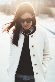 White collarless coat over black pants, sweater and gray blouse with pearls