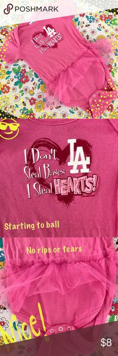 """Pink Infants Girls """"LA"""" Bodysuit Tutu 24 Mon """"I Don't Steal Bases I Steal Hearts - LA"""" Pink Bodysuit with a Tutu - 24 Mon -  If you are a LA Dodger's fan, you shouldn't pass this cutie up!!!! Pre-owned - Great Condition:  No holes, rips, staining, balling or piling. Tutu is in good shape - No Rips or Tears - Snaps work and are not rusted.  Smoke-Free  home.   😊Thank you for browsing my closet and have a good day!❤  ***************************************************** 💖 bundle & save 🌀…"""