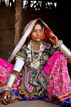 Portrait of a woman from the Marwada Meghwal Harijan tribe wearing traditional clothing and a large golden wedding ring through her nose in the village of Hodka, located roughly 60km from Bhuj in the Kutch District. Photography by Kimberley Coole.