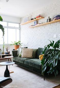 Sala de estar tem sofá de veludo verde, parede de tijolos e muitas plantas.