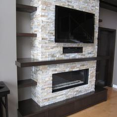 Dark wood, shelves and fireplace/TV combo.