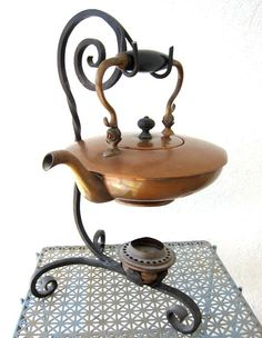Old world charm in this antique copper tea kettle on a wrought iron stand #teapot / Un'affascinante mondo del passato in quest'antico bollitore in rame su un basamento in ferro battuto #teiera