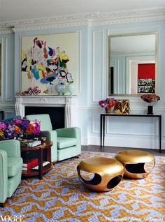 Living rooms with perfect pops of color: Blue walls, green armchairs and a modern patterned rug add personality to this eclectic home.