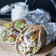 Two tempeh gyros rolled up in pita bread and foil stuffed with all the fixings