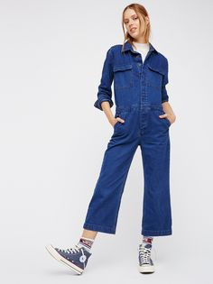Denim Coverall   Long sleeve denim jumpsuit featuring hidden button closures down the front and double breast pockets. Hip pockets.