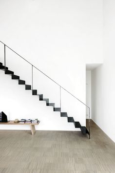 simplicity, thin black metal staircase against a white background, narrow  black railing forming a geometric outline