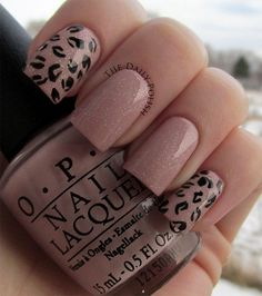 Leopard print inspired winter nail art design. The nails have pink nail polish as the base color while silver dust nail polish is also added on top. Black nail polish is then used to paint on the leopard prints.