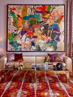 un tapis joyeux en couleurs, tableau abstrait, sofas beiges et deux tables rectangulaires