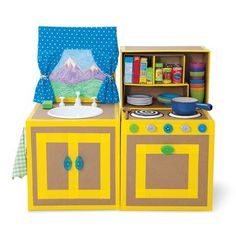 """cardboard box kitchen stove and sink with """"cabinet"""" space. Doors & edges are lined with duct tape. Knobs are plastic bottle lids. Sink is plastic bowls and burners are plastic plates inverted."""